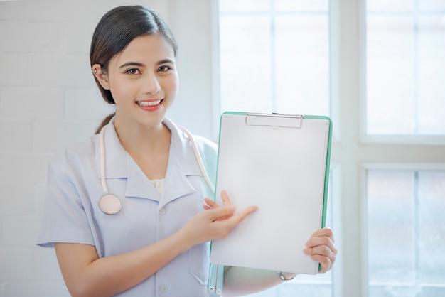 Doutor fêmea que mostra a prancheta com copyspace.