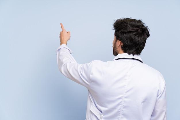 Doutor homem apontando para trás com o dedo indicador