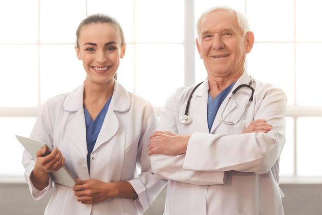 Doutor idoso e doutor fêmea novo bonito nos revestimentos brancos.