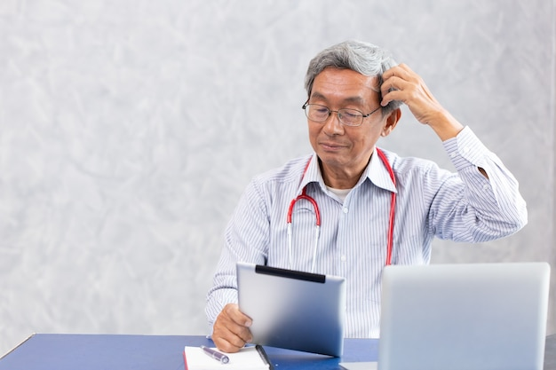 Doutor impensável, velho chinês usando tablet de computador com confuso complicado com o problema de problemas de notícias de quebra-cabeça de saúde de vírus corona.