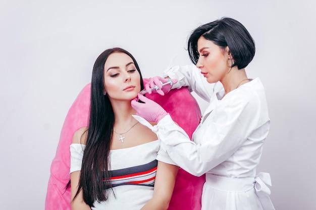 Doutor injetando em um lindo rosto de uma jovem. conceito de cirurgia plástica.
