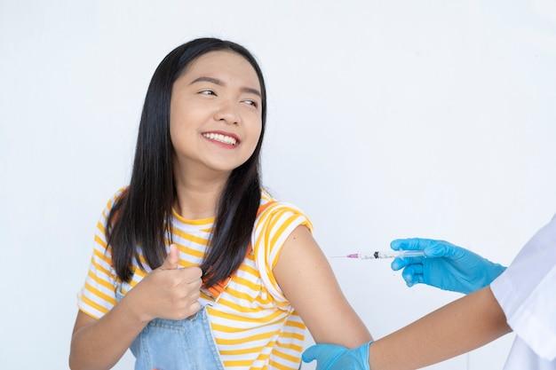 Doutor injetando vacinação no braço de uma jovem asiática em um estudante de fundo branco