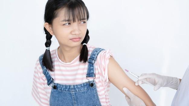 Doutor injetando vacinação no braço de uma jovem asiática no conceito médico do estudante de fundo branco