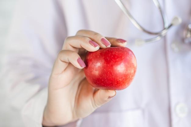 Doutor mão segurando uma maçã vermelha