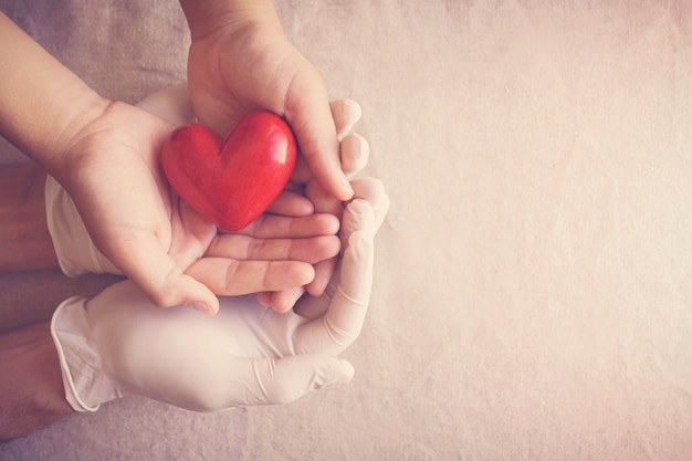 Doutor, mãos com luvas de criança, coração vermelho, seguro de saúde, conceito de doação