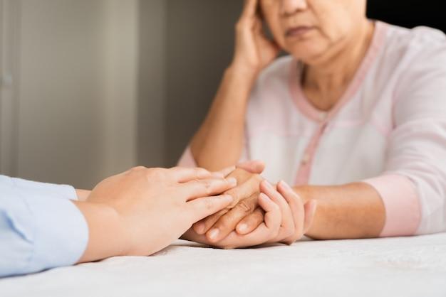 Doutor mãos juntas segurando paciente mulher sênior