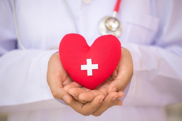 Doutor mãos segurando um coração vermelho com sinal de doador. conceito de saúde e médico.