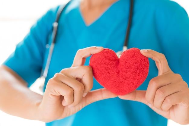 Doutor mãos segurando um coração vermelho. conceito de saúde e médico.