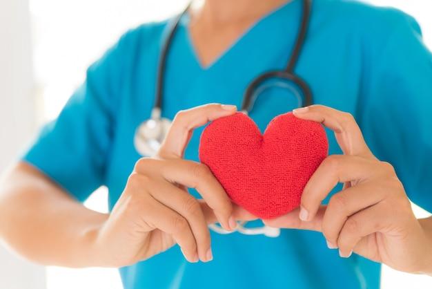 Doutor mãos segurando um coração vermelho. cuidados de saúde, conceito médico.