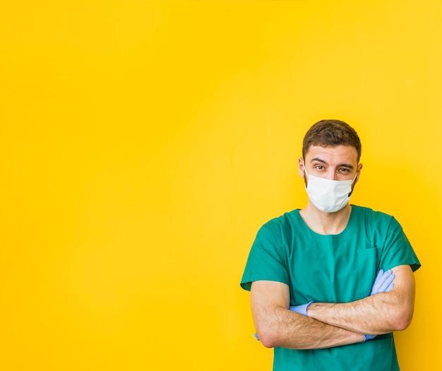Doutor masculino, em, máscara, com, braços cruzados