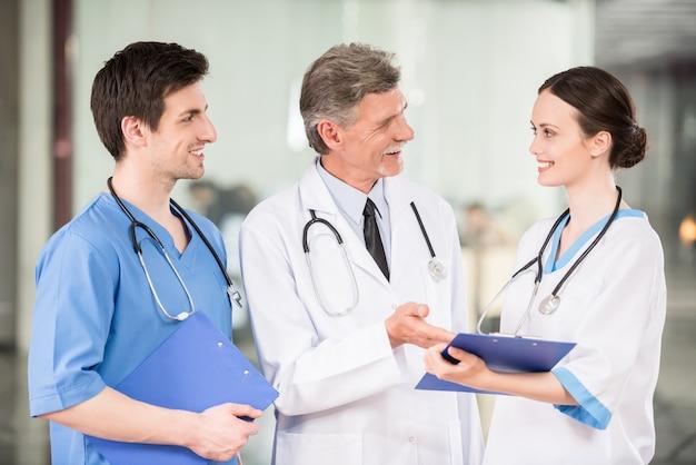Doutor masculino experiente com os internos médicos na clínica.