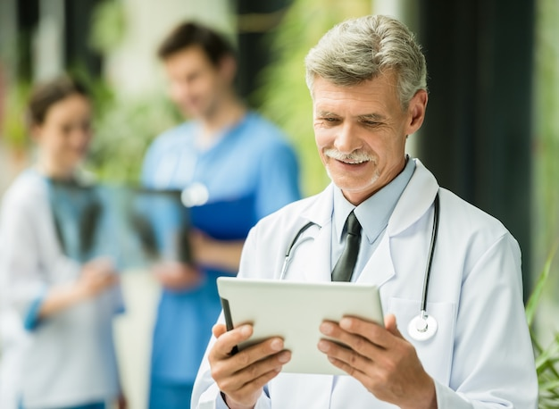 Doutor masculino maduro que olha a tabuleta digital.