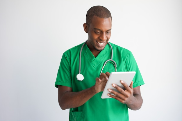 Doutor masculino preto de sorriso que usa o tablet pc. tecnologia no conceito de medicina.