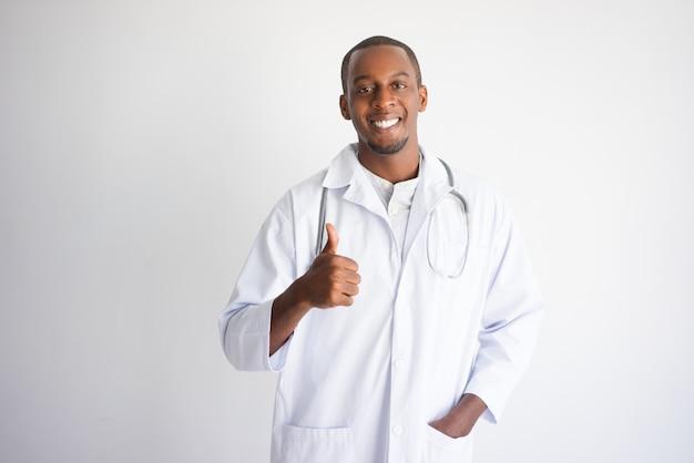 Doutor masculino preto feliz que mostra o polegar acima. conceito de publicidade de produtos médicos.