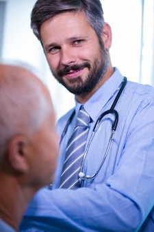 Doutor masculino que dá uma injeção a um paciente no hospital