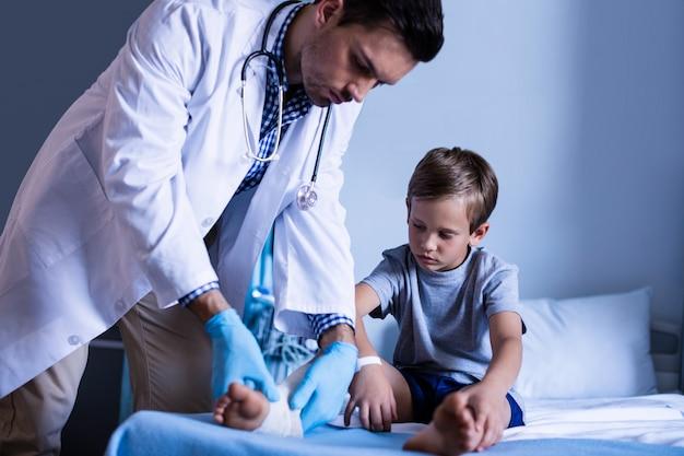 Doutor masculino que examina a perna do paciente