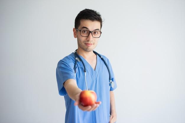 Doutor masculino satisfeito que guarda e que oferece a maçã vermelha borrada.