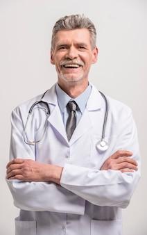 Doutor masculino sênior com as mãos cruzadas