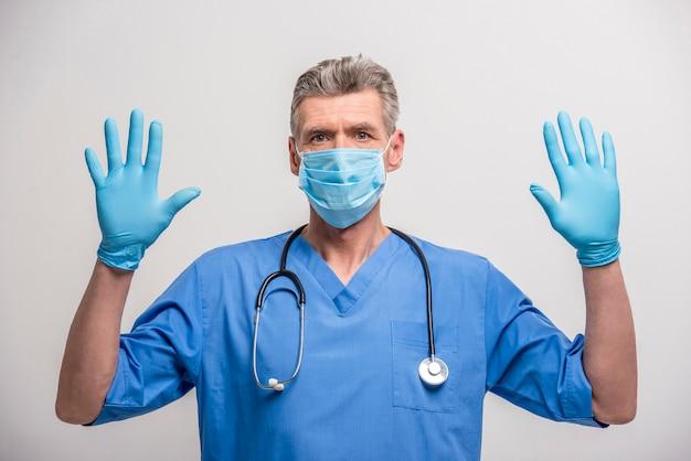 Doutor masculino sênior na máscara do cirurgião e nas luvas de borracha.