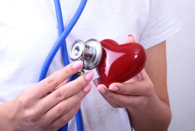 Doutor medicina feminina, segure, em, mãos, vermelho, brinquedo cabeça coração, e, estetoscópio