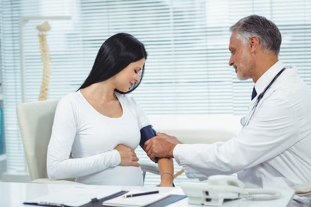 Doutor, medindo, pressão, de, mulher grávida, em, clínica