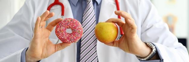 Doutor no escritório que guarda à disposição a filhós cor-de-rosa contra o close-up vermelho da maçã. produtos que não podem ser consumidos no conceito de certas doenças
