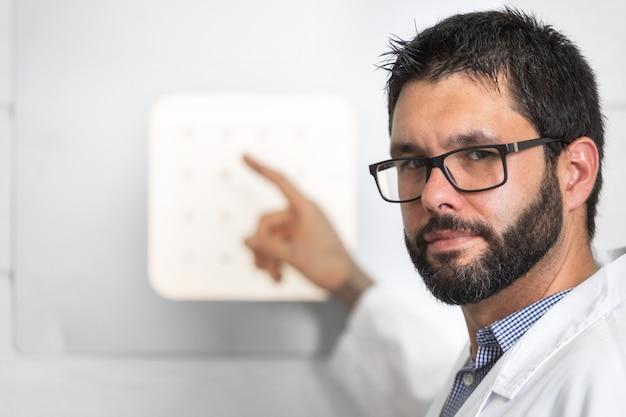 Doutor optician with letter chart que conduz uma verificação do teste do olho.