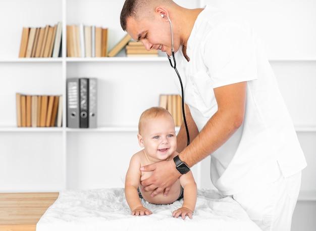 Doutor ouvindo bebê sorridente com estetoscópio