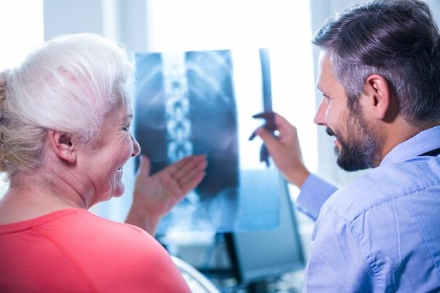 Doutor que discute raios-x com o paciente