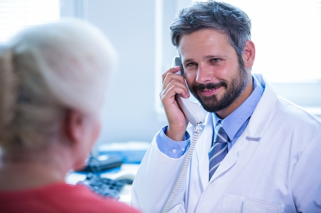 Doutor que fala no telefone fixo no escritório médico no hospital