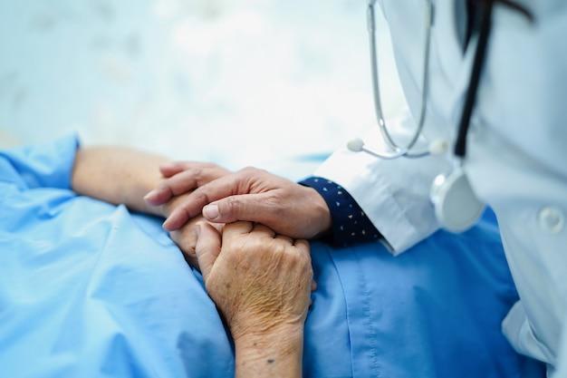 Doutor que guarda as mãos tocantes paciente superior ou idoso asiático da mulher da senhora idosa com amor, cuidado.