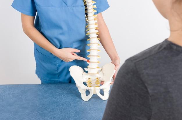 Doutor que mostra uma hérnia em um esqueleto a um paciente.