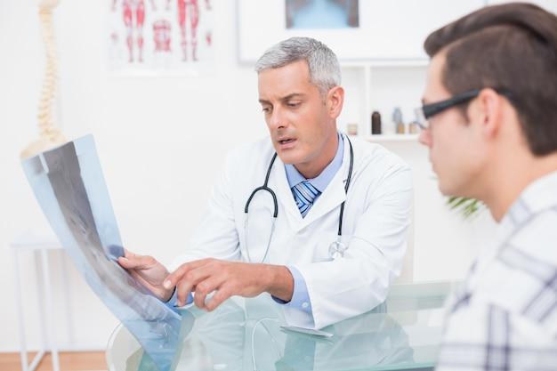 Doutor que mostra xrays ao paciente