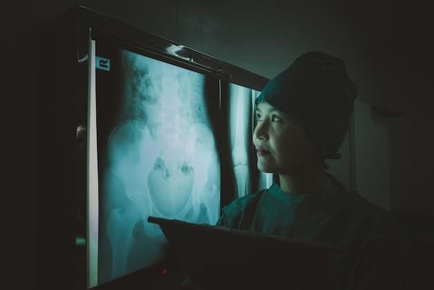 Doutor que olha o filme de raio x abdominal paciente no departamento da radiologia no hospital.