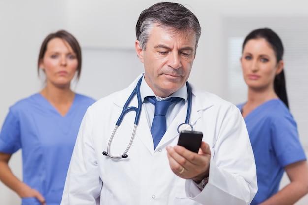 Doutor que olha o telefone com sua equipe de enfermeiras