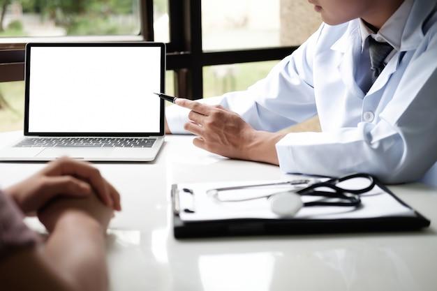 Doutor que usa a discussão da tabuleta do computador algo com paciente.
