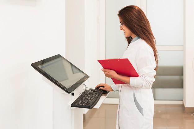 Doutor, segurando a área de transferência e trabalhando no computador
