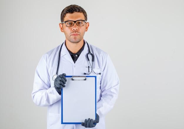 Doutor, segurando a área de transferência vazia nas mãos no roupão branco médico