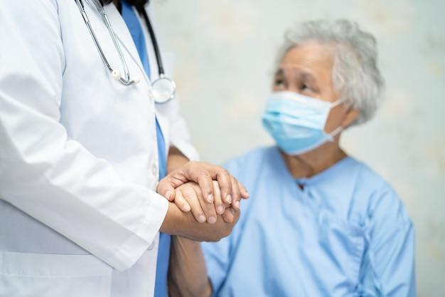Doutor, segurando a mão de uma paciente asiática usando máscara facial para proteger o covid-19 coronavirus.