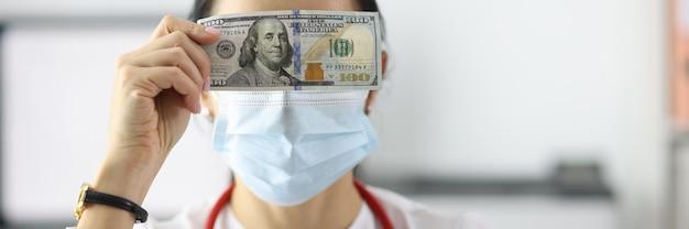 Doutor, segurando a nota de dólar perto de seus olhos em clínica closeup. conceito de corrupção entre profissionais de saúde
