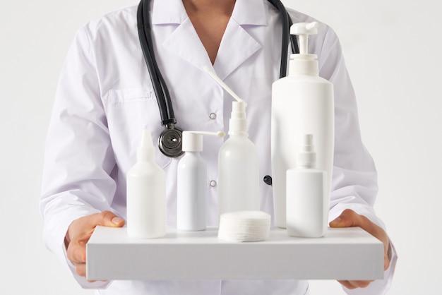 Doutor, segurando muitas garrafas de desinfetantes para as mãos e sabonete líquido