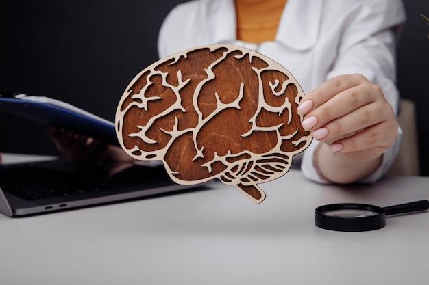 Doutor, segurando o cérebro de madeira. a importância do conceito de diagnóstico precoce.