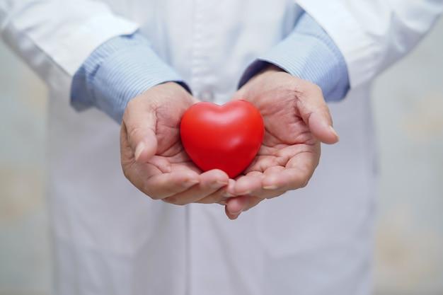 Doutor, segurando o coração vermelho na mão no hospital de enfermagem.
