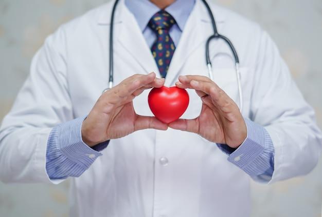 Doutor, segurando o coração vermelho na mão no hospital.