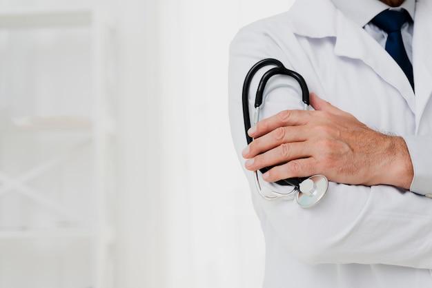 Doutor, segurando o estetoscópio com cópia-espaço