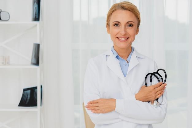 Doutor, segurando o estetoscópio no braço, olhando para a câmera
