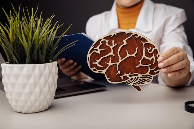 Doutor, segurando o modelo de madeira do cérebro. conceito de saúde.