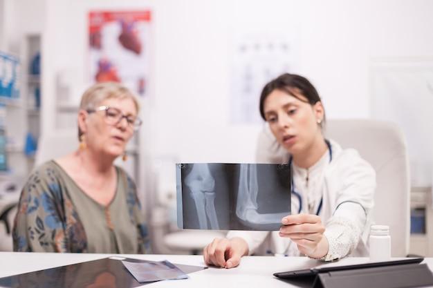 Doutor, segurando o raio-x e conversando com o paciente sênior sobre lesão no joelho no escritório do hospital. médico falando sobre terapia com mulher madura.