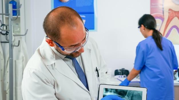 Doutor segurando o tablet com raio-x mostrando ao paciente enquanto a enfermeira prepara as ferramentas em segundo plano. estomatologista apresentando radiografia dentária a uma velha usando aparelho moderno em clínica estomatológica