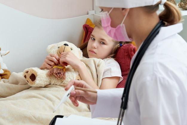 Doutor, segurando o termômetro e verificar a menina doente. menina doente na cama com febre, medir a temperatura
